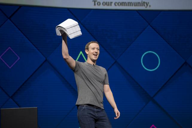 Mark Zuckerberg, chief executive officer and founder of Facebook Inc., holds up a stack of papers while speaking during the F8 Developers Conference in San Jose, California, last year.