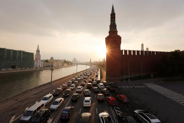 A highway beside the Moskva river and Kremlin, right, in the early evening in Moscow.