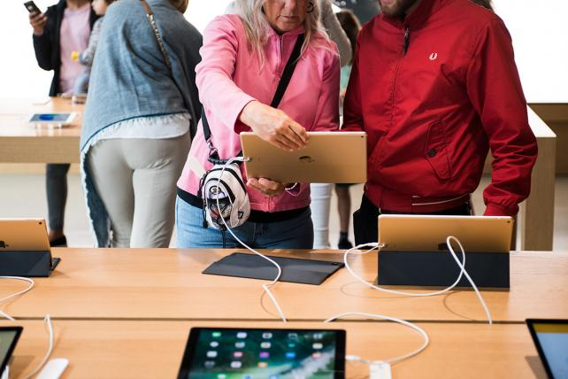 Customers view an Apple Inc. iPad Pro tablet at the company's Williamsburg store in the Brooklyn borough of New York.