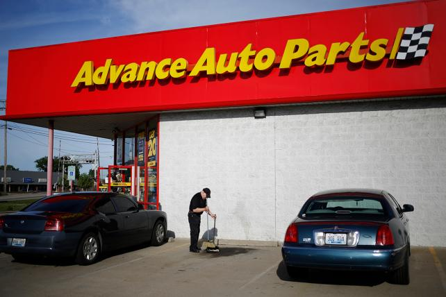 An employee sweeps the parking lot outside an Advanced Auto Parts Inc. store in Shepherdsville, Kentucky, U.S., on Monday, May 22, 2017.