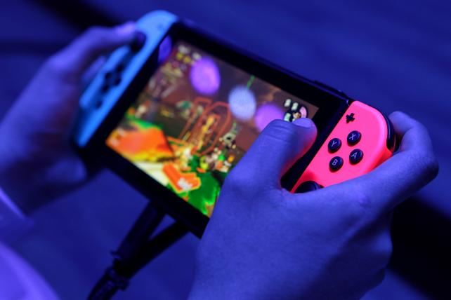 An attendee plays on a Nintendo Co. Switch video game console during the E3 Electronic Entertainment Expo in Los Angeles, California, U.S., on Wednesday, June 14, 2017.