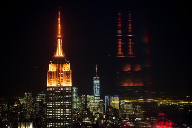 The spires of the Empire State Building, left, and One World Trade Center, center, are lit in orange to promote New York's bid for Amazon's second headquarters on Oct. 18.