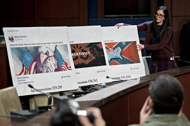 A staff member arranges a display showing social media posts during a House Intelligence Committee hearing on Wednesday.