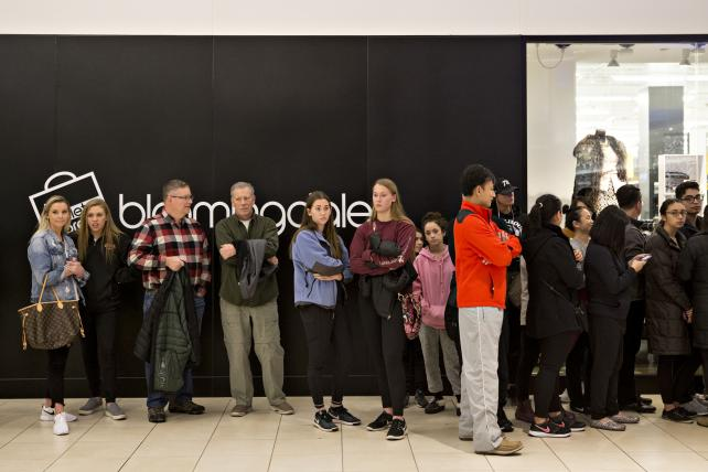 Shoppers wait in line to enter a store at the Fashion Outlets of Chicago mall in Chicago on Thanksgiving, now the unofficial kickoff to Black Friday for many.