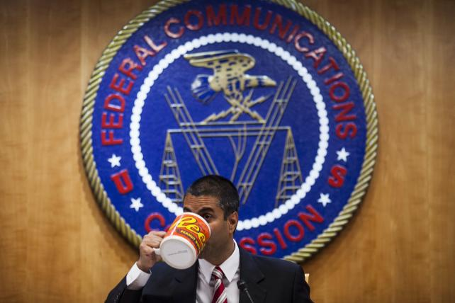 Ajit Pai, chairman of the Federal Communications Commission, drinks from an oversized coffee mug during an open meeting in Washington, D.C.