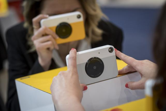 An exhibitor, left, takes a photograph of an attendee using the Eastman Kodak Co. Printomatic instant print camera during the 2018 Consumer Electronics Show in Las Vegas in January 2018.