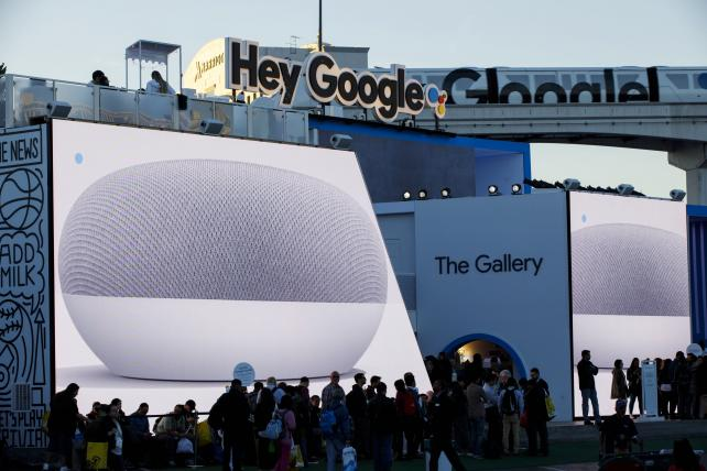 Alphabet Inc.'s Google Home Mini smart speakers are displayed on screens as attendees stand in line to enter the company's exhibit at the Consumer Electronics Show in Las Vegas last week.
