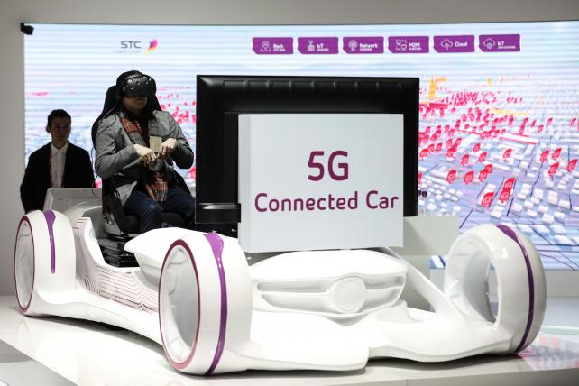 An attendee wears a VR headset for a 5G connected car experience on the Saudi Telecom Co. stand during the opening day of the Mobile World Congress in Barcelona on Monday.