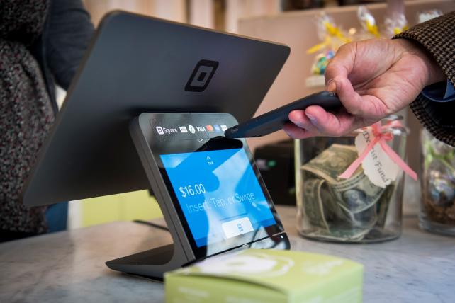 A customer inserts a credit card into Square Inc. device while making a payment.
