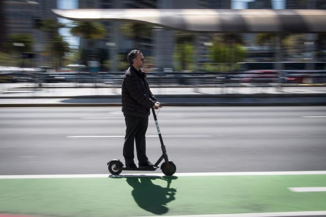 A person rides a Bird Rides shared electric scooter on the Embarcadero in San Francisco in April. GPS-enabled scooters and bicycles are spreading across several major U.S. cities, driven by a wave of venture capital into a handful of companies.