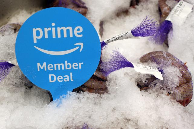 A sign alerts Amazon Prime members of a special deal on shrimp during the grand opening of a Whole Foods Market in Burbank, California, last month. Amazon bought the chain last summer. The company has also set its sights on sectors such as pharmacies and advertising.