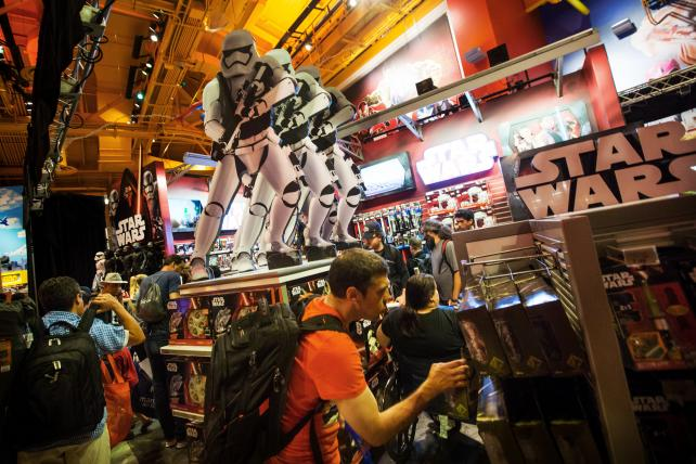 Attendees look at merchandise from the Walt Disney Co. Star Wars movie franchise during a 'Force Friday' event at a Toys R Us.