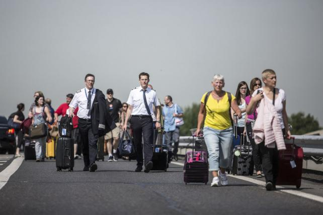Passengers and crew walk with their luggage outside of Charles de Gaulle airport near Paris.