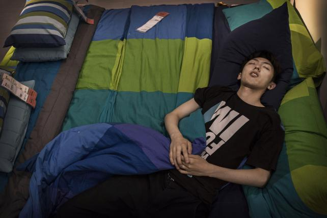 A Chinese shopper sleeps on a bed in the showroom of the Ikea store on July 6, 2014 in Beijing