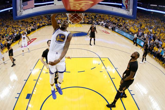 Kevin Durant dunks the ball as LeBron James watches.