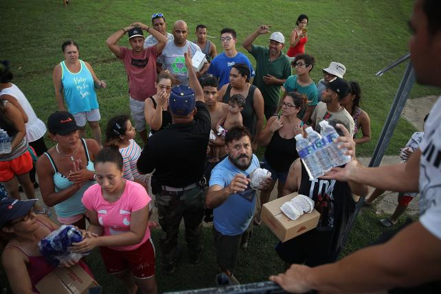 Hurricane survivors receive food and water being given out by volunteers and municipal police on Thursday in Toa Baja, Puerto Rico.