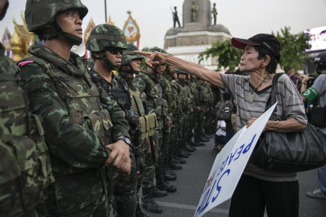 A protester confronts Thai soldiers during an anti-coup demonstration.