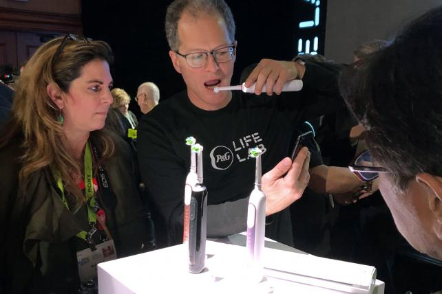 A P&G employee showing off its smart toothbrush, which connects to your phone.
