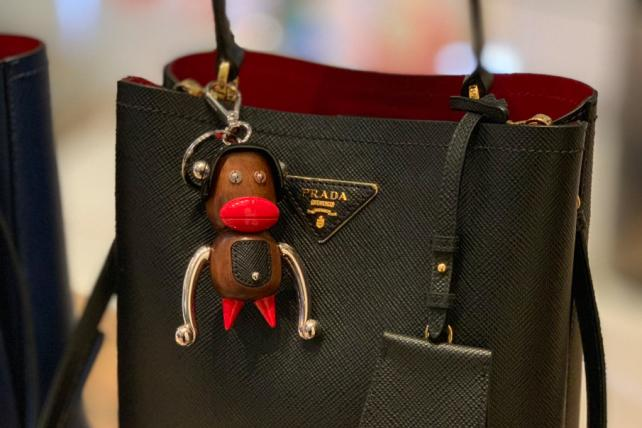 Pradamalia appearing in a Prada store, attached to a bag.