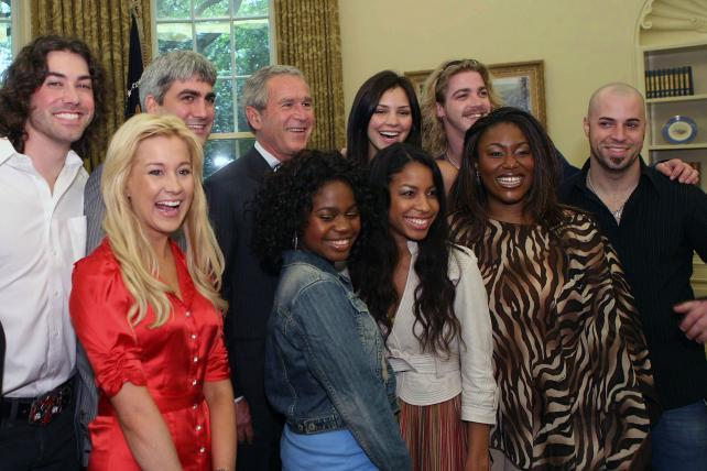 President George W. Bush poses with the 'American Idol' finalists in the Oval Office on July 28, 2006, in Washington, D.C. From left to right in the back row are Ace Young, Taylor Hicks, President Bush, Katherine McPhee, and Bucky Covington, and from left to right in the front row are Kellie Pickler, Paris Bennett, Lisa Tucker, Mandisa Hundley and Chris Daughtry.
