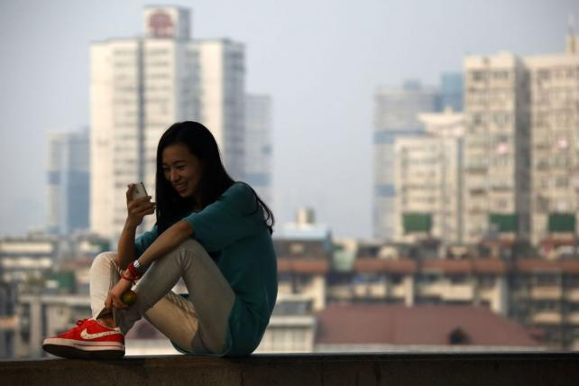 A woman checks her phone in Wuhan, China.