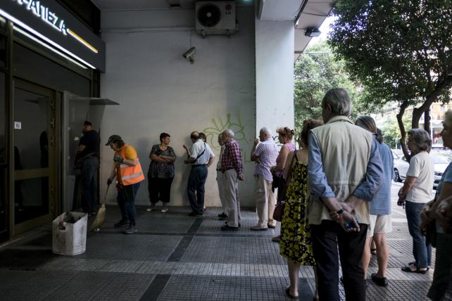 One of Greece's biggest supermarket chains is providing free bottles of water to people who wait in line to withdraw cash from ATMs.
