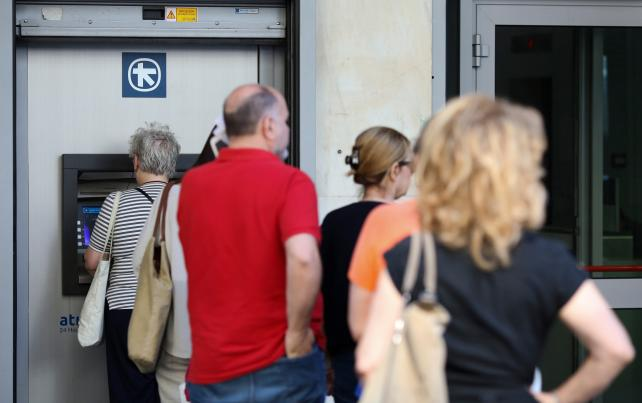 Customers wait at an ATM outside a closed bank branch in Athens.