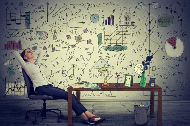 Young business woman relaxing at her desk in her office - Stock image