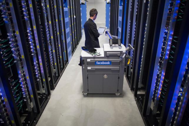 An employee inspects a tool and maintenance box, also known as a 'crash cart,' between server racks at Facebook's data center near the Arctic Circle in Lulea, Sweden.