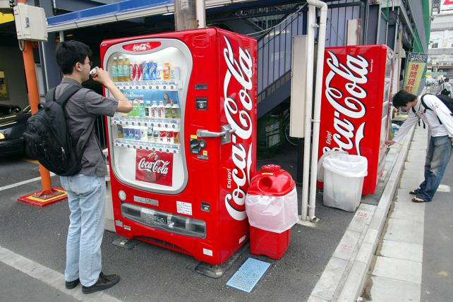 Tokyo residents purchase soft drinks from a Coca-Cola vending machine in Tokyo