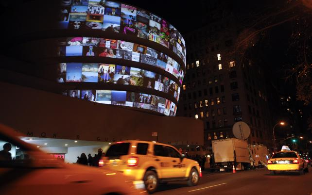 Taxis drive by as YouTube clips play during an exhibit on the exterior of the Guggenheim Museum in 2010.