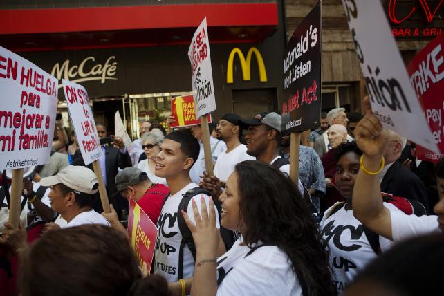 Demonstrators hold signs during a protest in front of a McDonald's in New York last September. Protesters clamoring for higher fast-food wages were arrested for blocking traffic during nationwide demonstrations.
