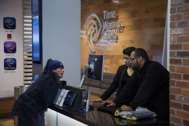 Employees assist a customer at a Time Warner Cable store in New York.