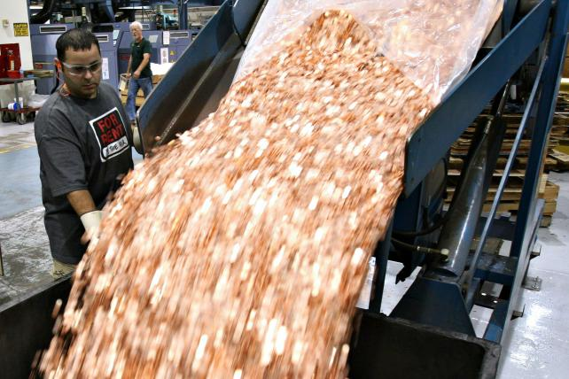 A pit driver at the U.S. Mint transfers one cent blanks before they are struck into pennies in Philadelphia.