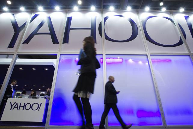Pedestrians pass the Yahoo pavilion at Mobile World Congress in February 2014.